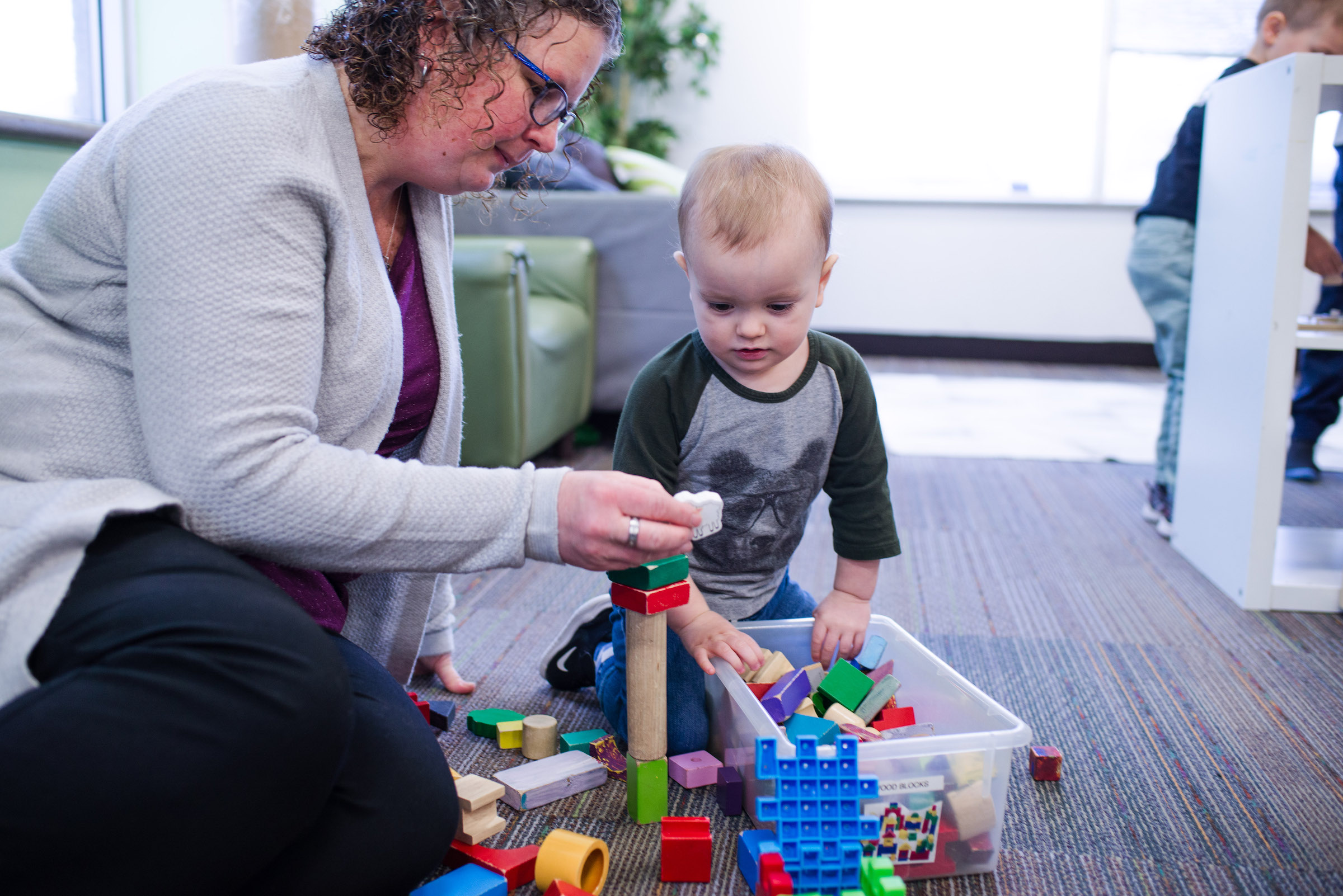 Educator guides baby's learning with bricks