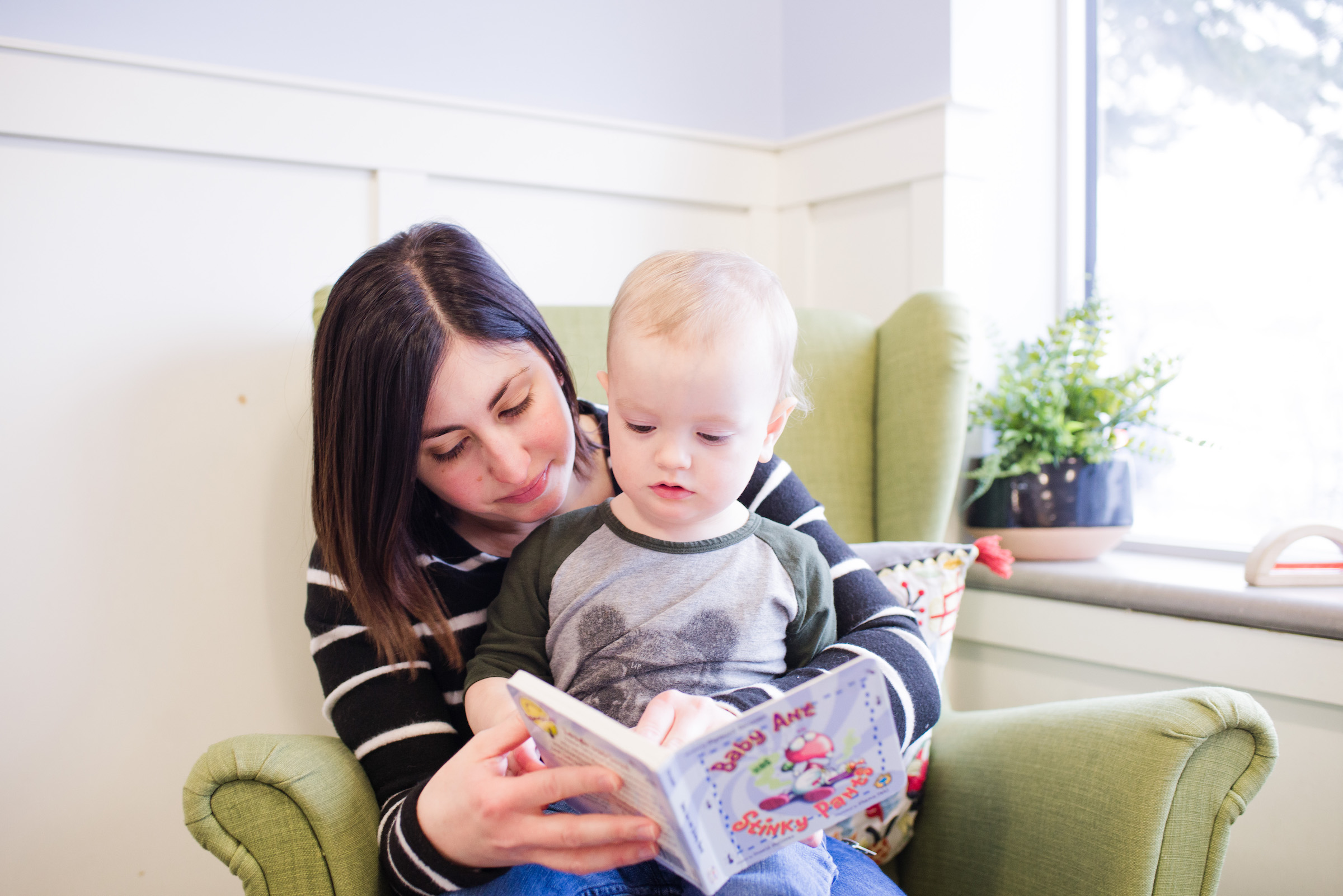 Caregiver reads to baby in Brightling infant room