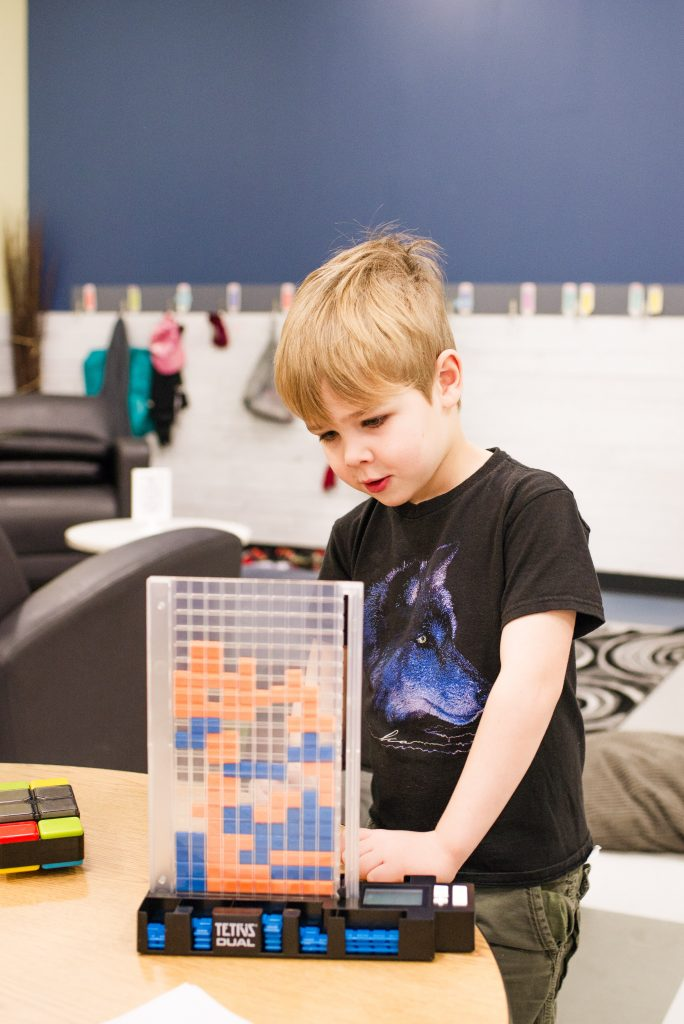 A child works on a spatial-relations puzzle.