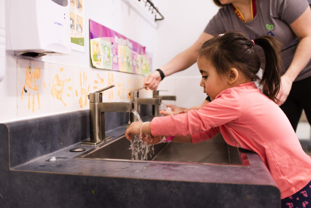 A caregiver helps a child at Brighting's child-accessible hand-washing station.