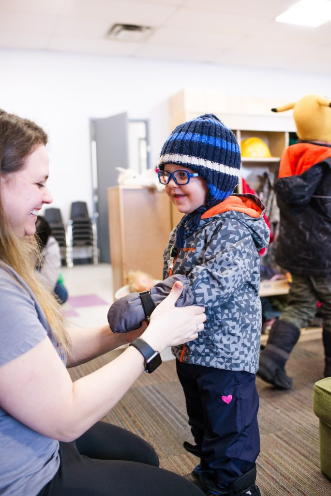 A Brightling caregiver helps a child get ready to go outdoors.