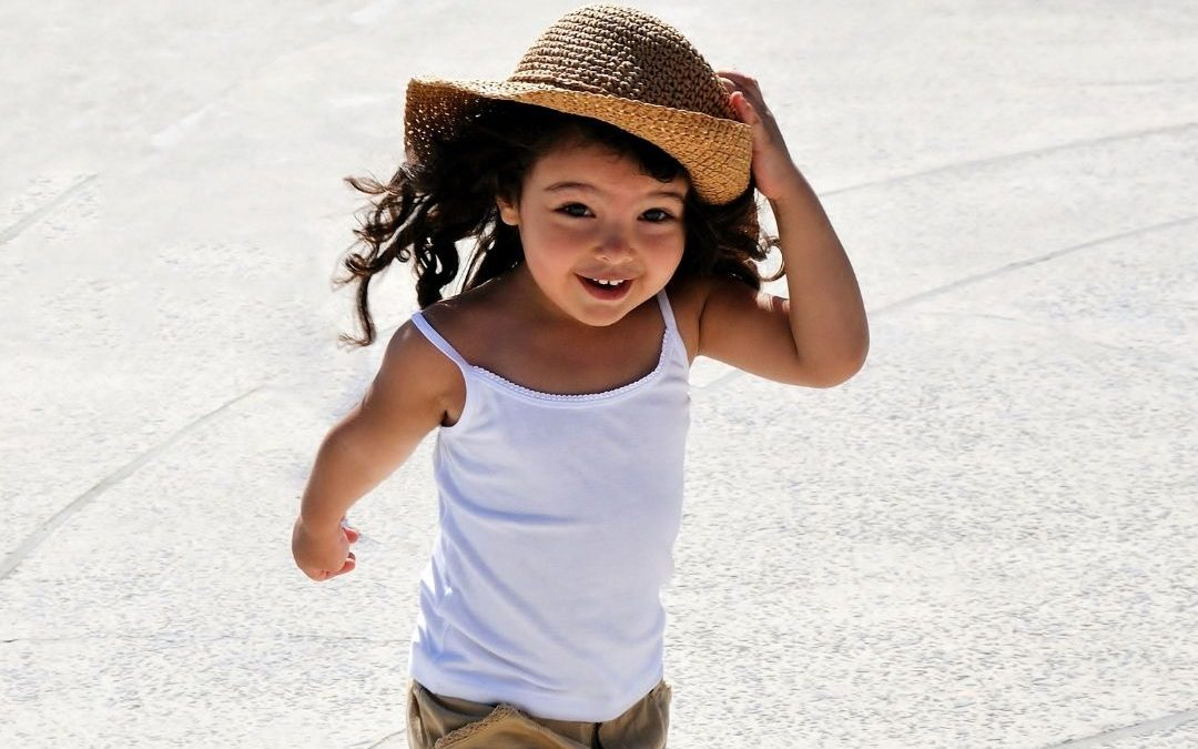kid running with straw hat on