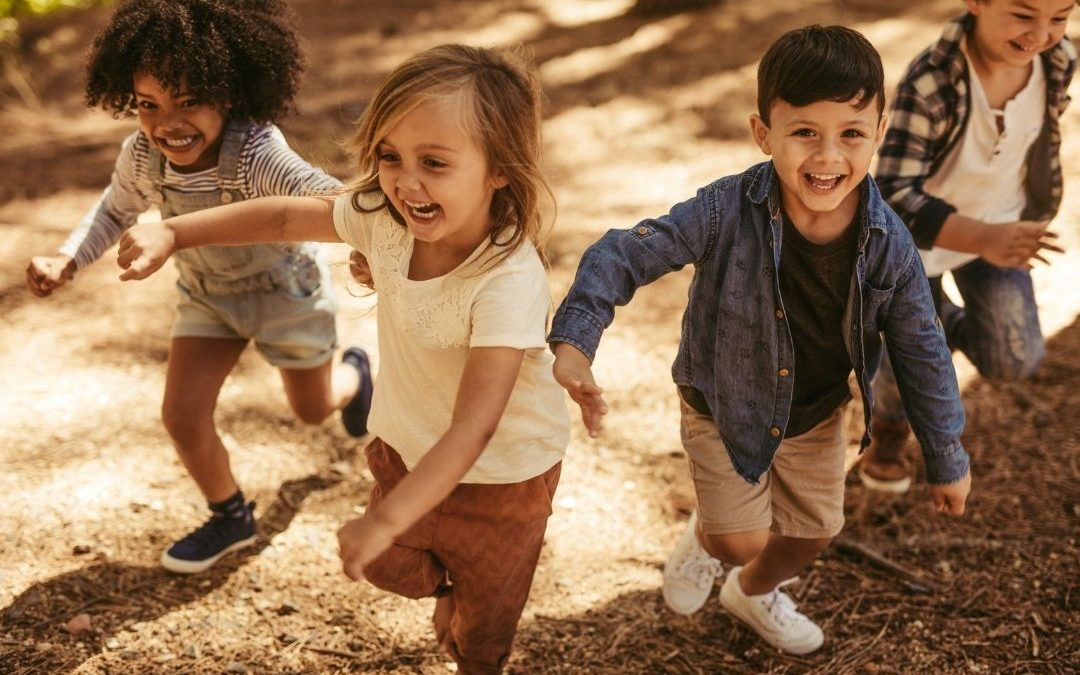 Four kids running in the woods with similes on their faces