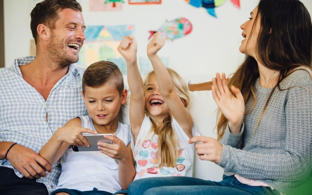 Two parents laughing while two kids smile