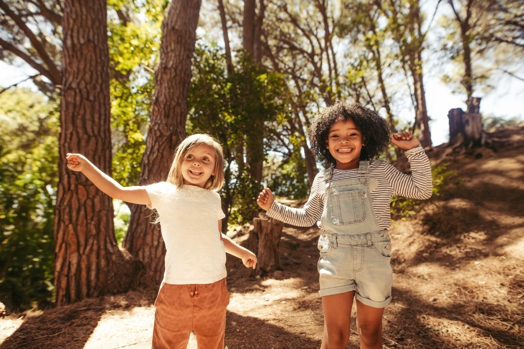 two girls jumping in the forest