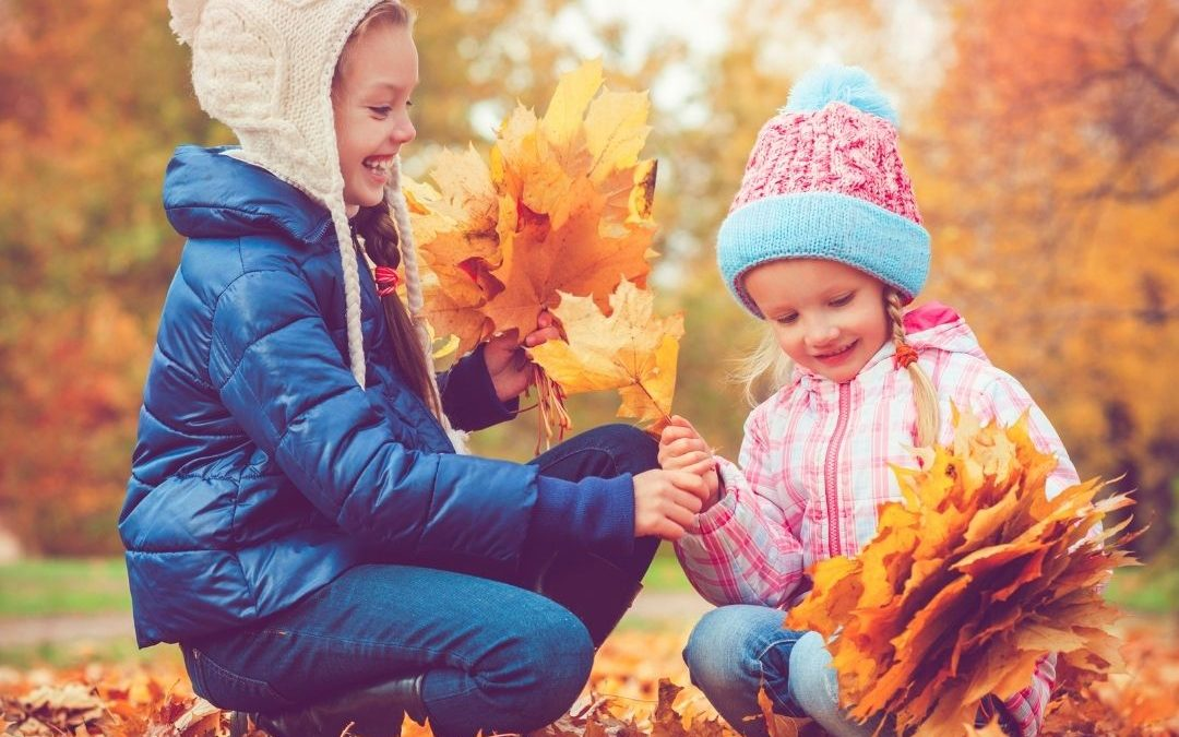 two kids playing in fall leaves